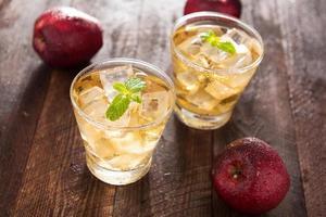 Apfelsaft und Äpfel auf Holztisch foto