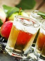 kühler erfrischender Apfelsaft mit Eis und Obst foto