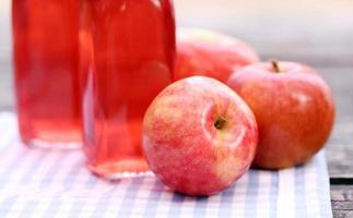 Flaschen mit roten Getränken und einigen Äpfeln foto
