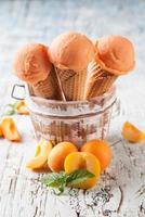Aprikosenfrische Eiskugeln in Zapfen auf Holz foto
