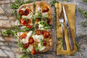 Pizza mit Tomaten und Rucola foto