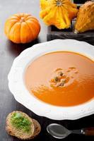 Kürbissuppe und rohe Kürbisse foto