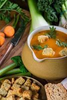 frische cremige Karottensuppe auf rustikalem Holztisch