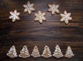 Weihnachtshintergrund mit Keksen verziert mit Zuckerguss, auf einem Holzbrett.