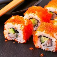 Sushi-Rolle mit Krabben, Avocado, Gurke und Tobiko.