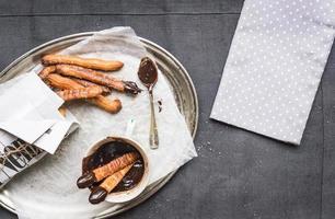 Churros mit Schokoladensauce auf einer Metallplatte foto