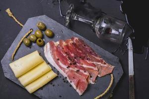 Schinkenarrangement mit verschüttetem Käse, Oliven und Wein foto