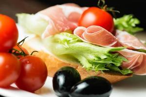 Schinkensandwich mit Tomaten und Oliven aus der Nähe foto