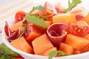 Melonensalat mit Tomaten und Schinken foto