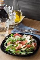 Rucola-Salat mit rasiertem Parmesan und Schinken-Crudo foto