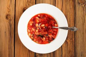 Portion hausgemachte russische rote Rübensuppe Borschtsch mit Bohne foto