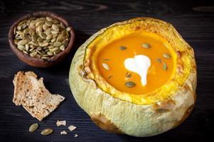 Kürbissuppe gebacken im Kürbis auf hölzernem Hintergrund foto
