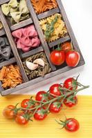 verschiedene italienische Pasta und Spaghetti-Tomaten in Holzkiste foto