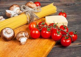 Nudelzutaten - Kirschtomaten, Pilze, Knoblauch, Brokkoli, Käse auf foto