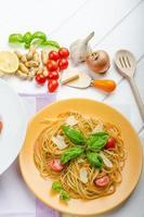 Zitronennudeln mit Kirschtomaten, Basilikum und Nüssen foto