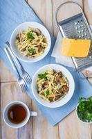 Nudeln mit Pilzen, Käse und frischer Petersilie foto