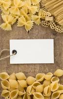 rohe Nudeln und Preisschild auf Holz foto