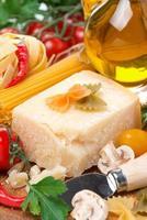 Parmesan, Gewürze, Tomaten, Olivenöl, Nudeln, frische Kräuter foto