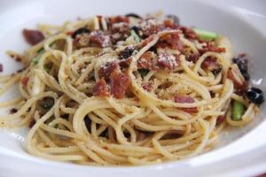 Spaghetti unter Rühren mit würzigem Schinken gebraten foto