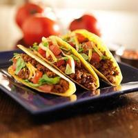 drei Rindfleisch-Tacos mit Käse, Salat und Tomaten foto
