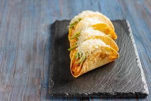 mexikanische Tacos mit Fleisch, Bohnen, Avocado, Käse und Tomatensauce
