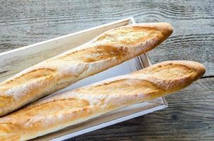 zwei Baguettes auf dem Holztablett foto