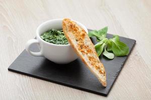 sautierter Knoblauch-Spinat-Teller, gebackene Brotscheibe mit geschmolzenem Käse