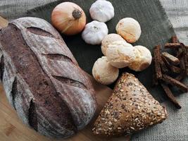 Brot, Zwiebeln, Knoblauch und Cracker auf braunem Grund foto