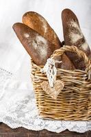 Weidenkorb mit verschiedenen Arten von frisch gebackenem Brot foto