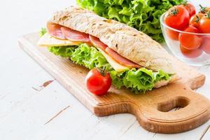 Sommersandwich mit Schinken, Käse, Salat und Tomaten foto