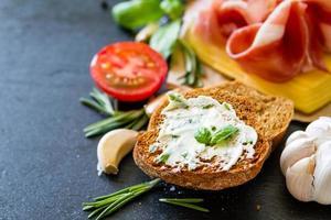 Sandwich-Zutaten - Baguette, Fleisch, Käse, Butter, Basilikum, Tomate, Knoblauch foto