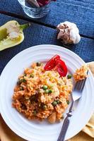 Risotto mit Huhn und Gemüse auf einem Teller mit Gabel foto
