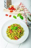 Spinat Tagliatelle mit Basilikum Pesto und Mini-Tomaten foto