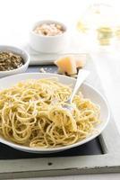 Spaghetti mit Pesto und Käse auf einem Teller, selektiver Fokus