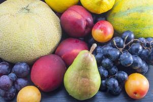 verschiedene Früchte auf dem dunklen Holztisch foto