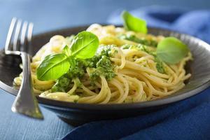 Spaghetti-Nudeln mit Pesto-Sauce über Blau foto