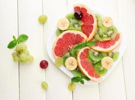 Auswahl an geschnittenen Früchten auf weißem Holztisch