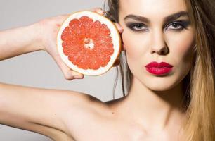 hübsches Mädchen hält Grapefruit in zwei Hälften geschnitten