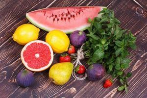 Grapefruits, Birnen, Zitronen, Wassermelonen, Feigen, Erdbeeren, Pampelmusen und Minze foto