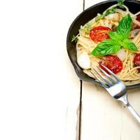 Spaghetti-Nudeln mit gebackenen Kirschtomaten und Basilikum foto