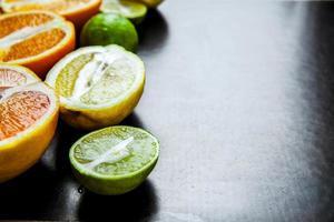 geschnittene Zitrusfrucht auf einem schwarzen Hintergrund. Essen foto