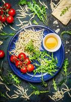 italienische Pasta in Schüssel mit Tomaten und Zutaten zum Kochen foto