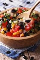 Salat mit schwarzen Bohnen, Avocado, Mais und Tomaten Nahaufnahme Verti foto