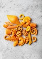 Haufen natürlich gefärbter orangefarbener Nudeln mit Karotten foto
