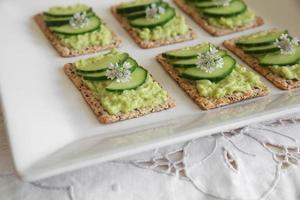 grüne Avocado-Vollkorncracker mit Korianderblüten foto