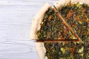 nützliche Torte mit Spinat, Käse auf Holztisch Nahaufnahme