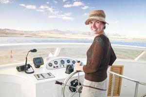 attraktive junge Frau, die ein Boot steuert foto