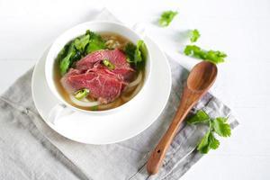 Rindfleischsuppe aus Vietnam, Pho, rohes Fleisch mit Koriander, Chili foto
