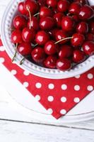 Süßkirschen auf Teller auf hölzernem Hintergrund foto