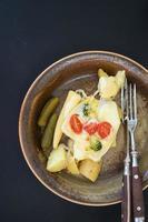 Salzkartoffeln und Gurken mit geschmolzenem Raclettekäse foto